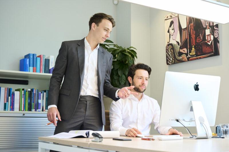 twee mannen in overleg achter bureau